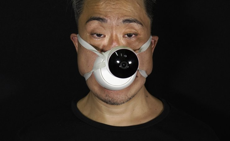 Edmond Kok, a Hong Kong theater costume designer and actor, wearing a face mask with a model CCTV (close circuit television) mounted on it in Hong Kong Thursday, Aug. 6, 2020. AP