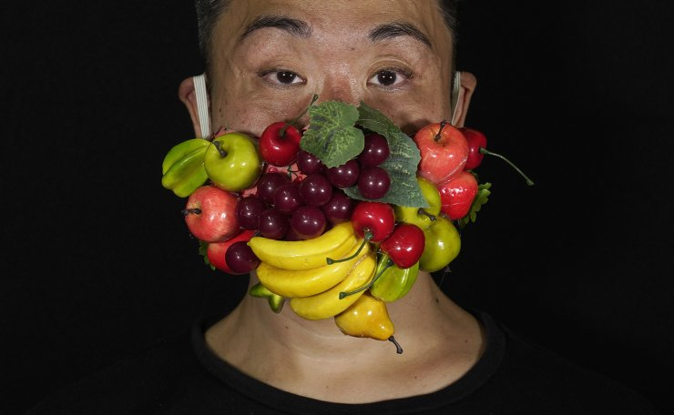 Edmond Kok, a Hong Kong theater costume designer and actor, wearing a face mask decorated with many different fruits in Hong Kong Thursday, Aug. 6, 2020. With little theater work because of the coronavirus pandemic, Kok has found a way to turn the now ubiquitous face mask into a creative opportunity. Since February, he has created more than 170 face masks inspired both by the pandemic and Hong Kong's political problems - not for actual use but as pieces of art. AP