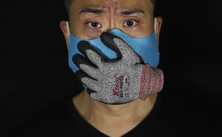 Edmond Kok, a Hong Kong theater costume designer and actor, wearing a face mask designed with a stuffed glove stuck on it, representing a hand over his mouth, looking scared, in Hong Kong Thursday, Aug. 6, 2020. AP