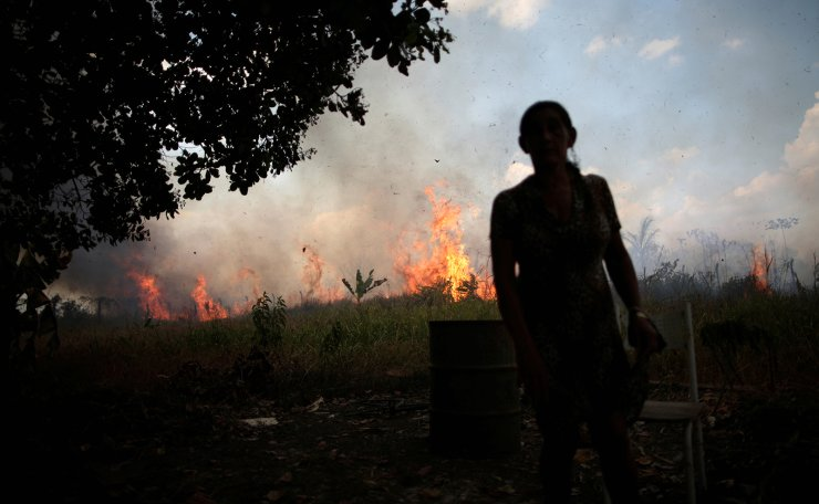 Miraceli de Oliveira reacts as the fire approaches her house in an area of Amazon rainforest, near Porto Velho, Rondonia State, Brazil August 16, 2020. Reuters