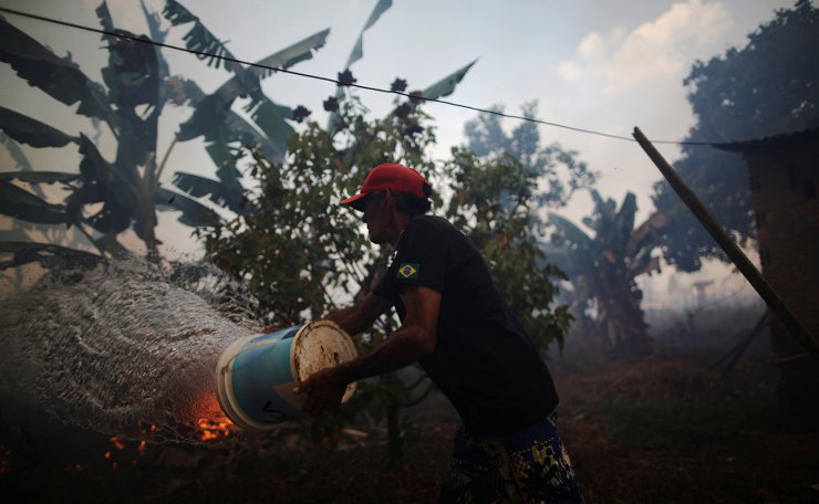 Rosalino de Oliveira throws water trying protect their house as the fire approaches in area of Amazon rainforest, near Porto Velho, Rondonia State, Brazil August 16, 2020. Reuters