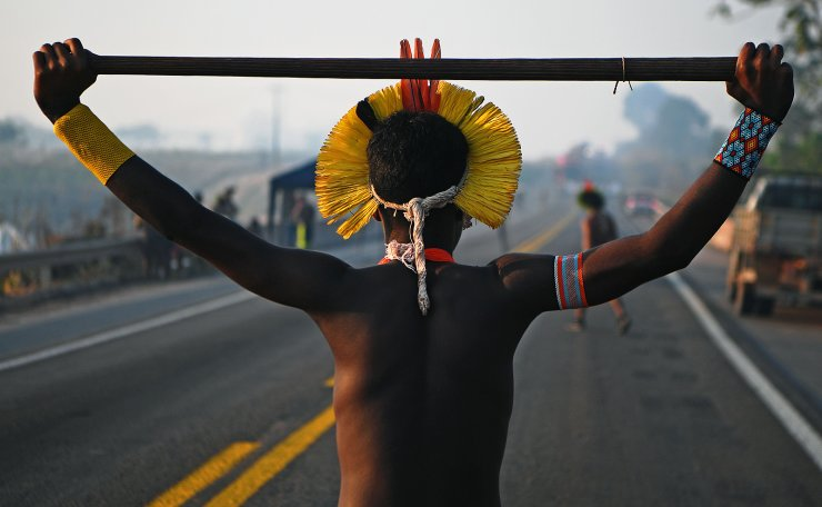 A member of the Kayapo tribe walks along the middle of blocked highway BR163 during a protest on the outskirts of Novo Progresso in Para State, Brazil, on August 17, 2020 amid the COVID-19 novel coronavirus pandemic. AFP