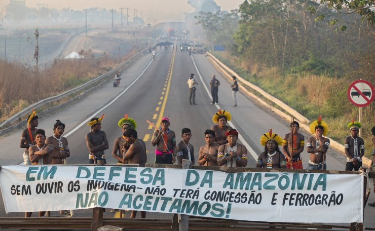 Kayapo Indigenous members block a road with a banner that reads in Portuguese 'Defending the Amazon. Without listening to Indigenous people, there will be no concession and nor grain railway,' near Novo Progresso, Para state, Brazil, Monday, Aug. 17, 2020. AP