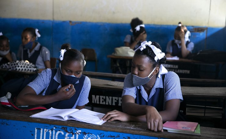 Students read at Lycee Marie Jeanne school on their first day back to school amid the COVID-19 pandemic in Port-au-Prince, Haiti, Monday, Aug. 17, 2020. AP