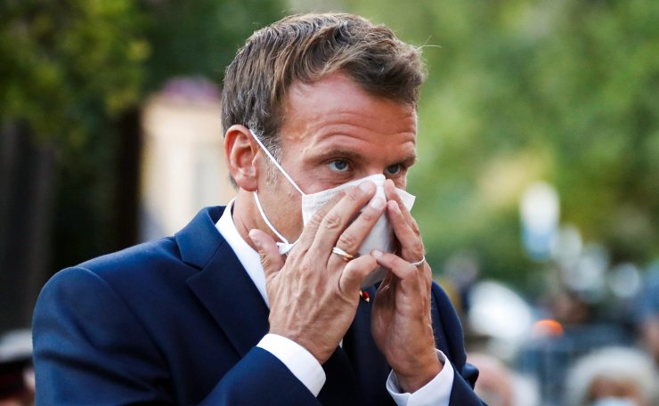 French President Emmanuel Macron adjusts his protective facemask as he attends the 76th anniversary of the Allied landings in Provence during World War II which helped liberate southern France, in Bormes-les-Mimosas on August 17, 2020. AFP