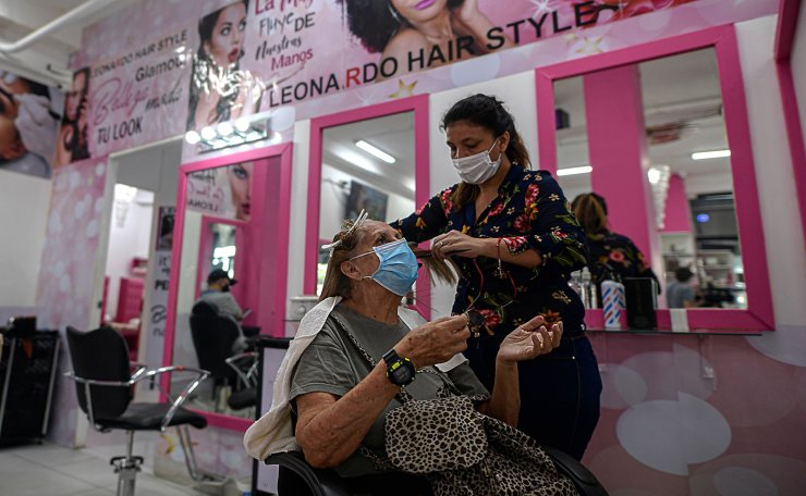 A hairdresser wearing a face masks styles the hair of a customer in Panama City, on August 17, 2020, as hairdressing salons were allowed to reopen amid the COVID-19 coronavirus pandemic. AFP
