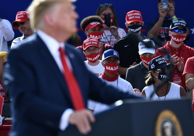People wear facemasks as US President Donald Trump delivers remarks on the economy at an airport hangar on August 17, 2020 in Oshkosh, Wisconsin. AFP