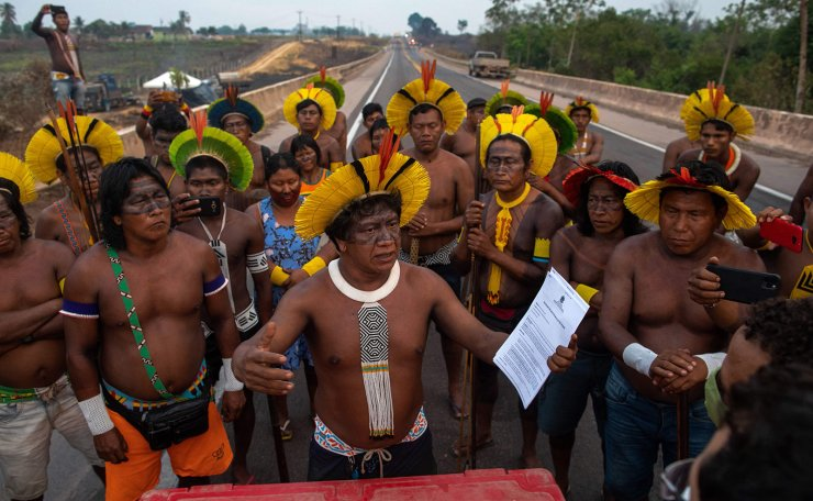 A member of the Kayapo indigenous tribe holds a request given by a judicial officer asking them  to clear the highway BR163 within 24 hours, during a protest in the outskirts of Novo Progresso in Para State, Brazil, on August 18, 2020 amid the COVID-19 novel coronavirus pandemic. AFP