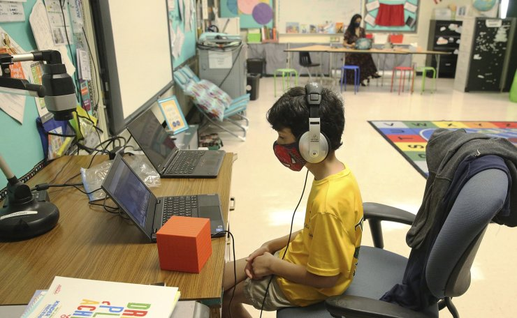 Nova Blanche Forman Elementary School teacher Attiya Batool, teaches her 4th grade class virtually as her son, Nabeel, does his second grade classwork online wearing a face mask and headphones during the first day of school in Broward, Wednesday, Aug. 19, 2020, in Davie, Fla. AP
