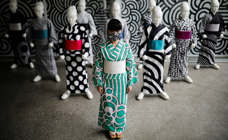 Japanese artist Hiroko Takahashi wears a protective face mask as she poses for a photograph in front of mannequins displaying yukata, a lighter kimono which she designed, at her studio in Tokyo, Japan July 1, 2020. Reuters