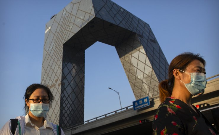People wearing face masks to protect against the coronavirus walk past the China Central Television (CCTV) Building in the central business district in Beijing, Friday, Aug. 21, 2020. Authorities in China's capital announced on Thursday that masks would no longer be mandatory outdoors as a virus outbreak in the country's northwestern region of Xinjiang appears to have been brought under control. AP
