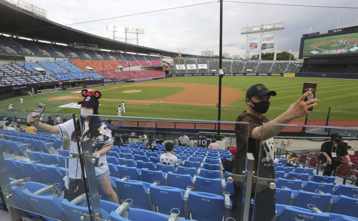 In this July 27, 2020, file photo, fans wearing face masks to help protect against the spread of the new coronavirus take a selfie before the KBO league game between Doosan Bears and LG Twins in Seoul.  AP