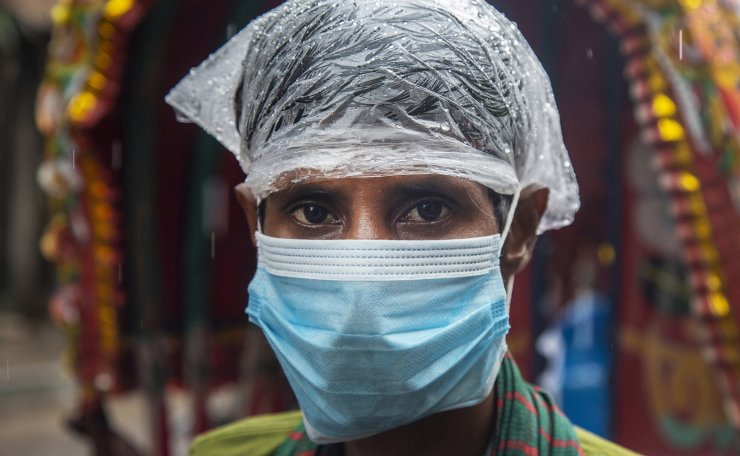 A rickshaw puller covers his head with plastic as he wears a face mask during the rain in Dhaka, Bangladesh, 22 August 2020. The summer monsoon season in Bangladesh is witnessed from June through mid-October. EPA