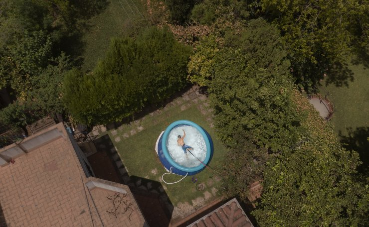 Ricardo D'hont swims in a neighbors plastic portable pool in Seville, Spain on Aug.11, 2020. The owners of the pool said that 'Due to the coronavirus we couldn't go to the beach or to other pools. If we hadn't been in pandemic we would never bought a plastic pool'. AP