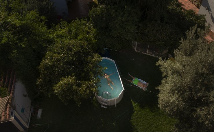 Manuel Caballos lays on the grass as Esperanza Lafrance swims in a plastic portable pool in the garden of their home in Seville, Spain on Aug. 11, 2020. Caballos had to cancel his vacation due the restrictions of the coronavirus and now says 'the pool is crucial to withstand the heat in the city'. AP