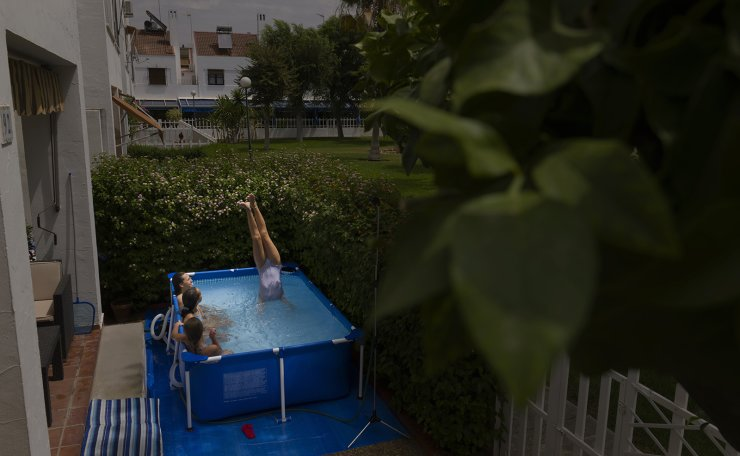 A group of young girls enjoy themselves in a portable plastic pool on a private patio in Seville, Spain on Aug. 11, 2020. Elena Tapia, the owner said that 'I bought the pool because of the Covid-19. The great thing to have it is that as the owner I don't have to keep any schedule and during the heat wave I can swim whenever I want'. AP