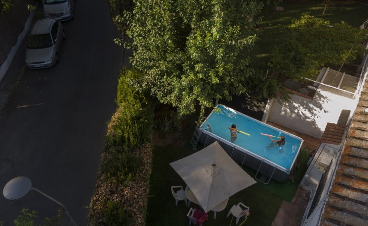Two young girls play in a portable plastic pool in the garden of a home in Seville, on Aug. 5, 2020. The owner Barbara Larraneta bought it 'like a lot of people in this city because of the heat, the covid and the lack of certainty about the summer and the restrictions'. AP