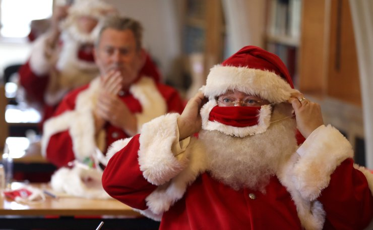 Santas use hand sanitiser and put on face masks as they attend a socially distanced Santa school training at Southwark Cahedral in London, Monday, Aug. 24, 2020.  AP