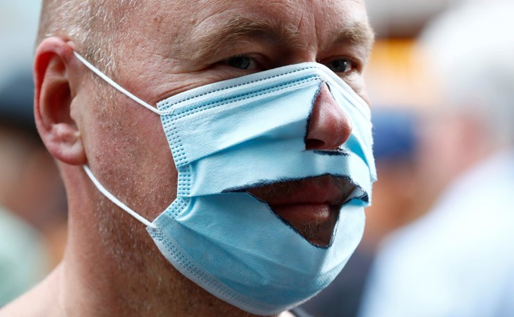 A demonstrator wears a mask that has been cut out as he attends a rally against the government's restrictions following the coronavirus disease (COVID-19) outbreak, in Berlin, Germany August 29, 2020. Reuters