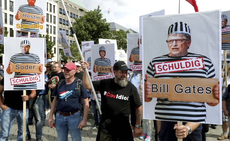 People attend a protest rally in Berlin, Germany, Saturday, Aug. 29, 2020 against new coronavirus restrictions in Germany, holding a sign with Bill Gates in prison clothes, reading 'Guilty'. Police in Berlin have requested thousands of reinforcements from other parts of Germany to cope with planned protests at the weekend by people opposed to coronavirus restrictions. AP