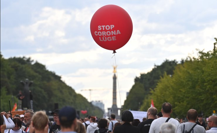 Protesters hold a floating ballon with a message on it which reads 'Stop the Corona lie' on the 17. Juni avenue in Berlin during a demonstration called by far-right and COVID-19 deniers to protest against restrictions related to the new coronavirus pandemic, on August 29, 2020. AFP