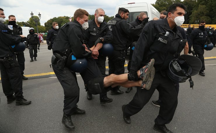 Police officers carry away a protester at an unregistered demonstration against government coronavirus regulations held next to the Siegesaeule, or Victory Column, in Berlin, Germany on August 30, 2020, one day after some 38,000 people, double the number expected, had gathered in Berlin to protest restrictions imposed to curb the spread of the coronavirus, such as the wearing of masks and social distancing. AFP