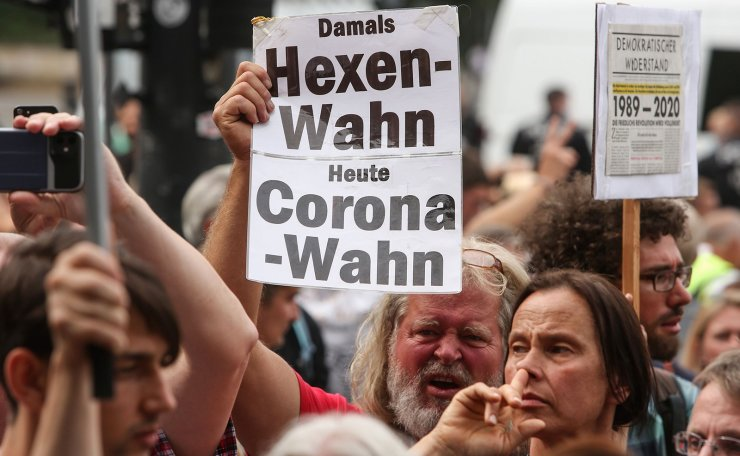 A protester holds up a sign reading 'Back then whitch craze, today corona craze' during an unregistered demonstration against government coronavirus regulations held next to the Siegesaeule, or Victory Column, in Berlin, Germany on August 30, 2020. AFP