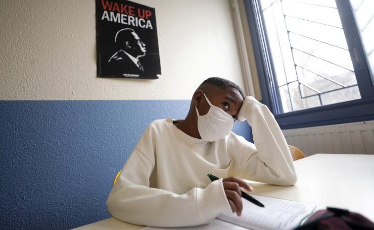 A secondary school student, wearing a protective face mask, works in a classroom at the College Henri Matisse school during its reopening in Nice as French children return to their schools after the summer break with protective face masks and social distancing as part of efforts to curb a resurgence of the coronavirus disease (COVID-19) across France, September 1, 2020. Reuters