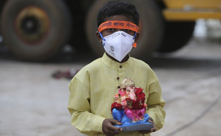 An Indian child wearing a mask as a precaution against the coronavirus carries an idol of elephant-headed Hindu god Ganesha to immerse in Saroornagar Lake on the final day of Ganesh Chaturthi festival in Hyderabad, India, Tuesday, Sept. 1, 2020.  AP