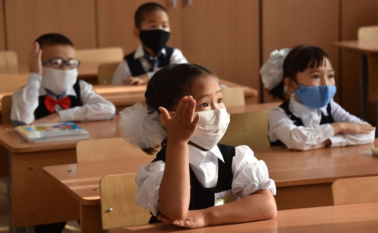Kyrgyz schoolchildren wearing a protective mask to prevent the spread of the novel coronavirus (covid-19), participate in a lesson on the first day of the new school year in Bishkek on September 1, 2020. AFP