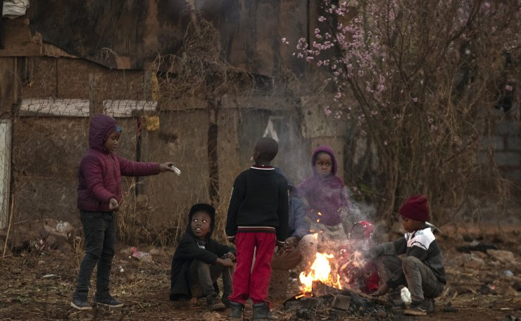 Children sit around a fire to warm themselves during a cold afternoon in Duduza township, east of Johannesburg, South Africa, Tuesday, Sept. 1, 2020, as bitterly cold weather continues for a second day. AP