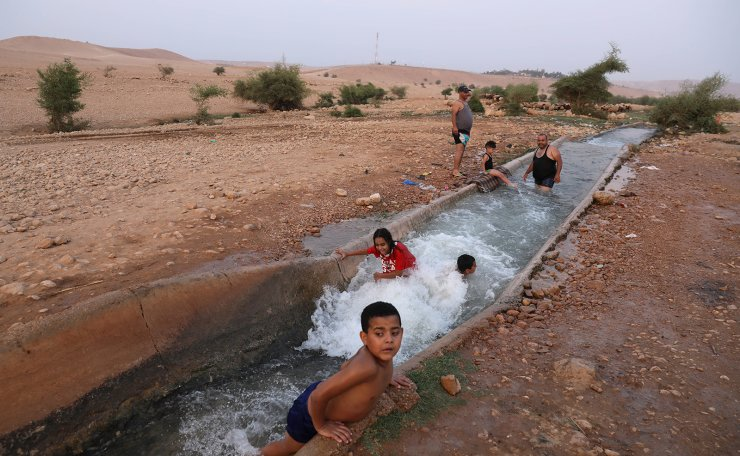 Palestinian children enjoy a swim in a water spring on a hot summer day as heavy heat wave hits the area near the Palestinian village of Al-Auja in the Jordan Valley, West Bank , 01 September  2020. EPA