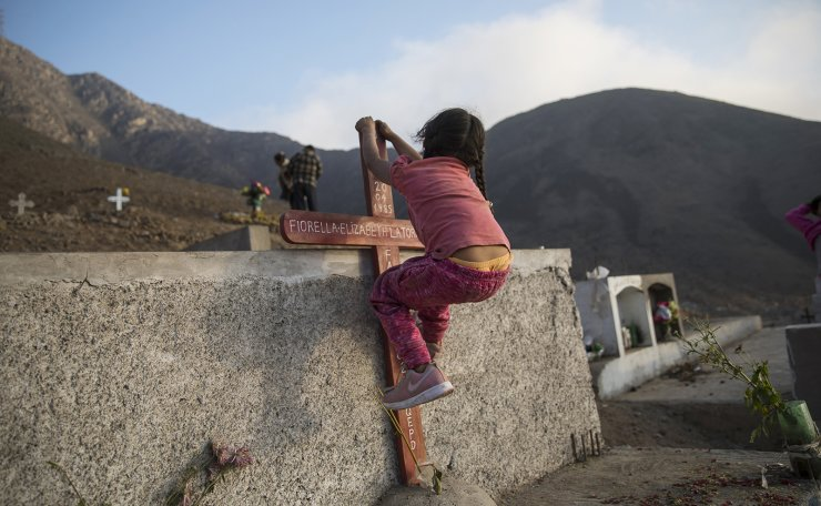Briana Vilcherrez climbs on a cross marking a tomb during a family visit to her father's grave who died due to symptoms related to the new coronavirus at the age of 49, at the 'Martires 19 de Julio' cemetery in the Comas district, on the outskirts of Lima, Peru, Wednesday, July 15, 2020. 'Briana and her brother Neymar love to visit their father's grave because they say they feel closer to him, and here they also have a large place to play, run and have fun, ' said Gloria Perz, the children's mother. AP