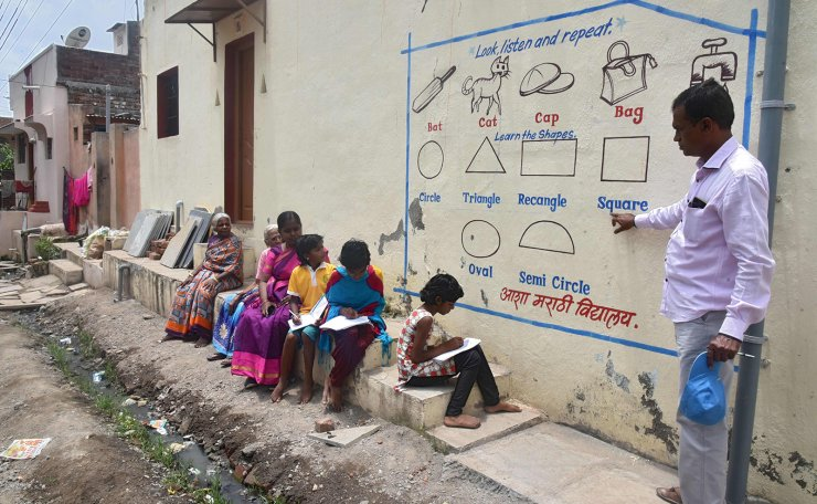 n this picture taken on August 27, 2020, Kalidas Chavdekar, a school teacher of Aasha Marathi Vidyalay points to a writing from textbooks of various subjects painted on the wall of a house to teach students who are unable to carry smartphones to attend online school classes amid Covid-19 coronavirus pandemic in Solapur, in Maharashtra state. Half a dozen children in an Indian village gather around their teacher as she points a stick at a lesson painted on a wall, one of many which are part of an unusual effort to help poor students keep up with their education amid the coronavirus pandemic. AFP