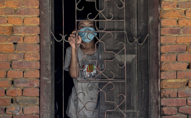 A child looks on from a window while devotees and riot police clash ahead of the Rato Machindranath chariot festival procession in Lalitpur, Nepal, 03 September 2020. EPA