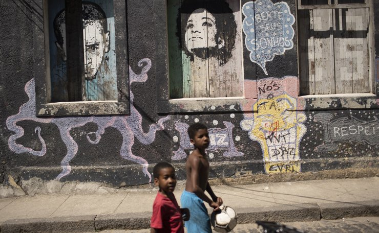 Children walk past a mural that reads 'Free you dreams' amid the new coronavirus pandemic at Morro da Providencia favela, Rio de Janeiro, Brazil, Thursday, Sept. 3, 2020. Rio de Janeiro is deploying a program to administer 20 thousand COVID-19 quick tests in the city's poor neighborhoods to track the progress of the disease. AP