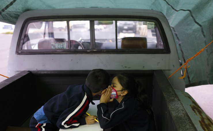 Aide Joselin Hernandez Moreno, right, writes on paper while using a donated tablet, as neighborhood volunteer Rebeca Rodriguez, left, works with siblings Axel and Paulina Mariano Ortiz in a pick-up truck bed repurposed into an educational space on the southern edge of Mexico City, Friday, Sept. 4, 2020. AP