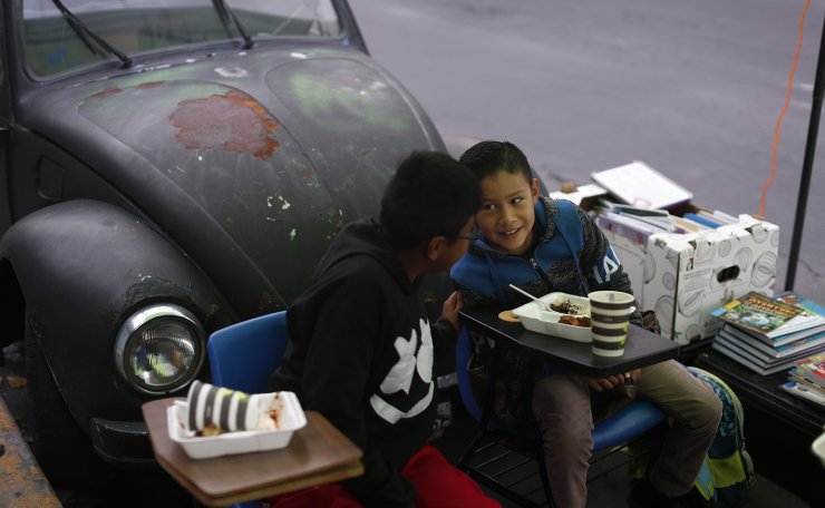 Brothers Bryan,  right, and Emanuel Quintana, talk as they eat a donated breakfast prior to a history lesson in front of 'Tortillerias La Abuela,' or Grandma's Tortilla Shop, on the southern edge of Mexico City, Friday, Sept. 4, 2020. Concerned about the educational difficulties facing children during the coronavirus pandemic, the couple who run the tortilla shop adapted several spaces outside their locale to provide instruction and digital access to locale children who don't have internet or TV service at home, a project which has attracted donations and a waiting list of students. AP
