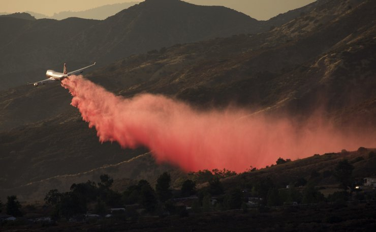An air tanker drops retardant at a wildfire burns at a hillside in Yucaipa, Calif., Saturday, Sept. 5, 2020. Three fast-spreading wildfires sent people fleeing and trapped campers in one campground as a brutal heat wave pushed temperatures above 100 degrees in many parts of California. AP