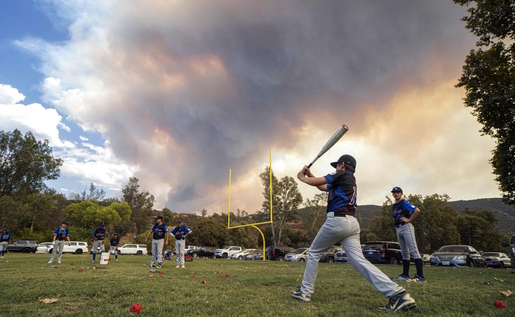 Little League players warm-up before a game as a brush fire  is ablaze in back at a field next to the Sycuan Casino on the Sycuan Indian reservation during the Valley Fire, near Dehesa, in San Diego, California on September 6, 2020.