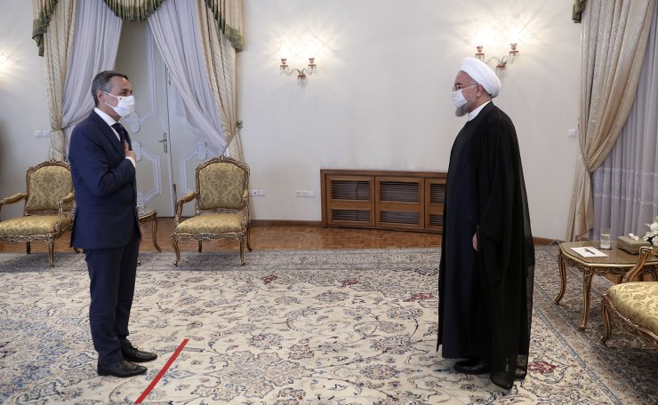 In this photo released by the official website of the office of the Iranian Presidency, President Hassan Rouhani, right, welcomes Swiss Foreign Minister Ignazio Cassis as they wear protective face masks to help prevent spread of the coronavirus, at the presidency office in Tehran, Iran, Monday, Sept. 7, 2020. AP