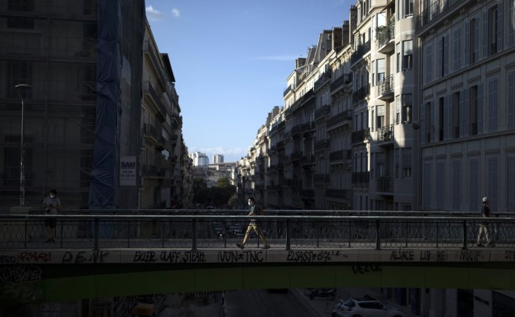 A man wearing a face mask walks across a pedestrian bridge in Marseille, southern France, Monday, Sept. 7, 2020. AP