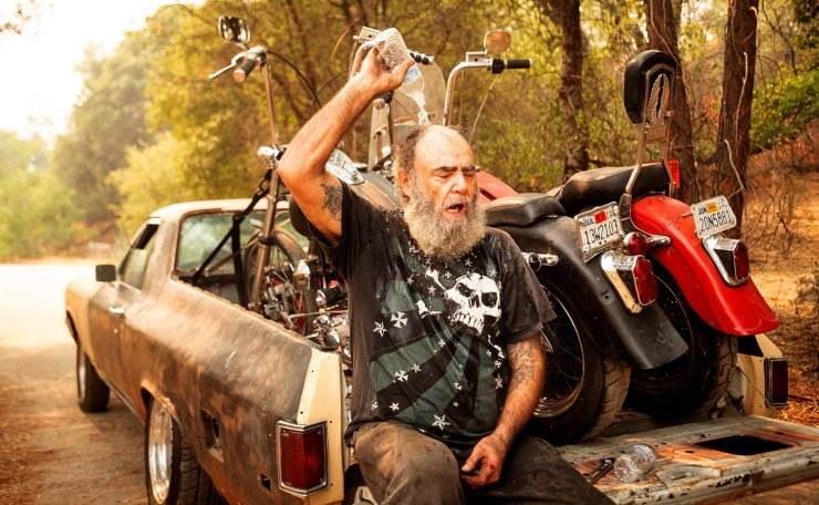 Jim Smart dumps water on his head to cool off after evacuating with two of his prized motorcycles during the Creek fire in the North Fork area of unincorporated Madera County, California on September 7, 2020. AFP