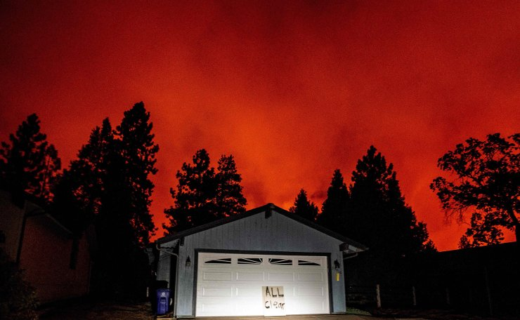 A home sits with an 'All Clear' sign on the front as fire approaches a neighborhood during the Creek fire in the Tollhouse area of unincorporated Fresno County, California on September 08, 2020. AFP