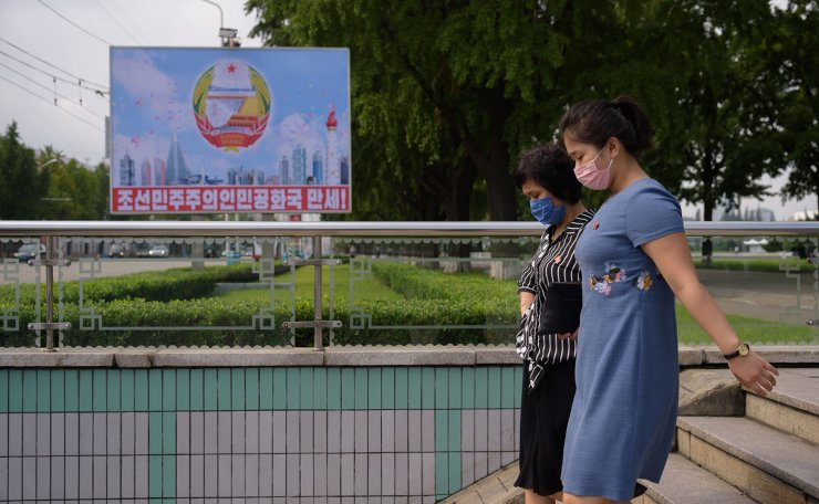 Two women wearing face masks enter an underpass before a poster commemorating the 72nd anniversary of the founding of North Korea, in Pyongyang on September 9, 2020. AFP