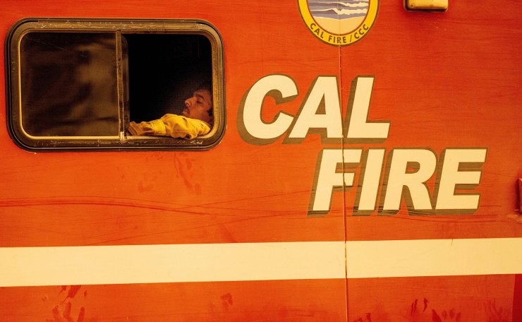A firefighter rests in his vehicle during the Bear fire, part of the North Lightning Complex fires, in unincorporated Butte County, California on September 09, 2020. AFP