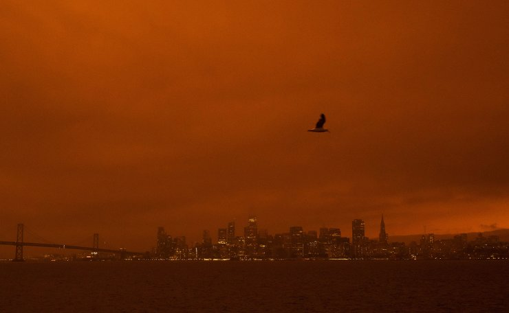 Smoke from various wildfires burning across Northern California mixes with the marine layer, blanketing the San Francisco skyline in darkness and an orange glow, seen from Treasure Island on September 9, 2020 in San Francisco, California. AFP