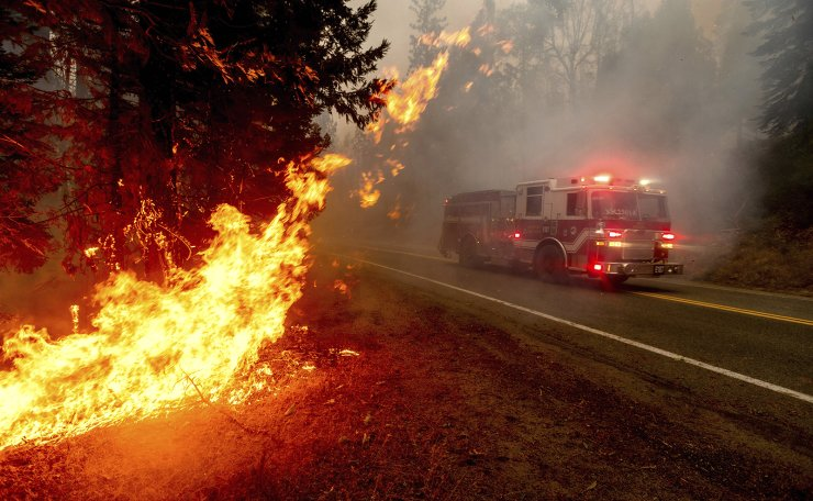 In this Sept. 7, 2020, file photo a firetruck drives along state Highway 168 while battling the Creek Fire in the Shaver Lake community of Fresno County, Calif. AP