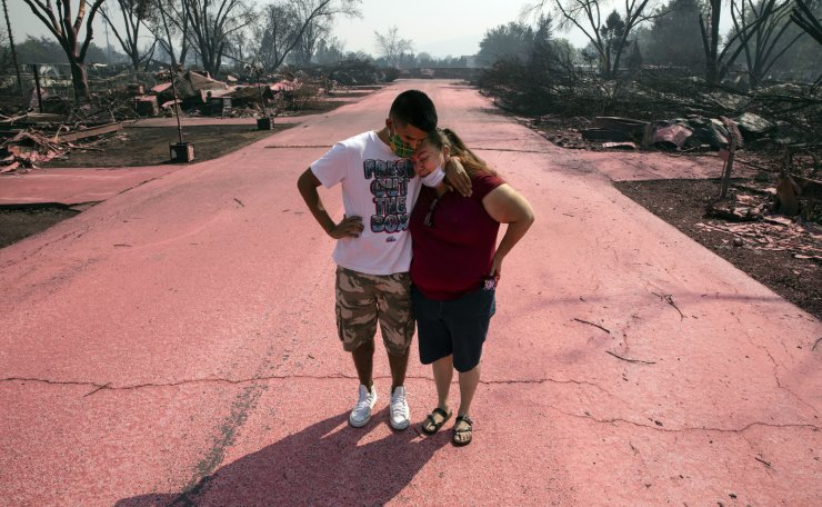 Maria Centeno, right, from Mexico, is consoled by her neighbor Hector Rocha after seeing their destroyed mobile homes at the Talent Mobile Estates, Thursday, Sept. 10, 2020, in Talent, Ore., after as wildfires devastate the region. AP