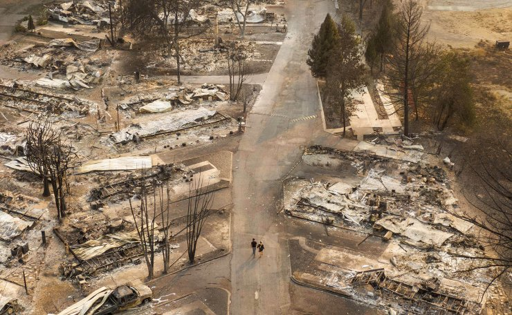 In this aerial view from a drone, people walk through a mobile home park destroyed by fire on September 10, 2020 in Phoenix, Oregon. Hundreds of homes in the town have been lost due to wildfire. AFP